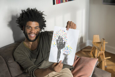 Man sitting on couch in living room showing children's drawing - SBOF00394