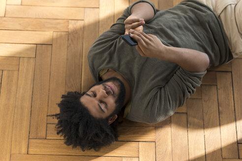 Man lying on floor with smartphone - SBOF00397