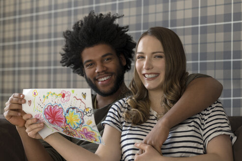 Smiling couple sitting on couch showing children's drawing - SBOF00400