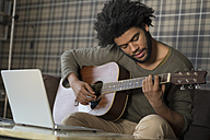 Man sitting in living room on sofa playing guitar in front of laptop - SBOF00403