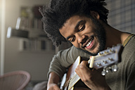 Smiling man playing guitar - SBOF00406