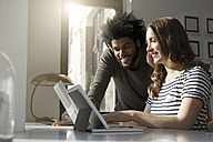 Smiling couple working at home with laptop and tablet - SBOF00409