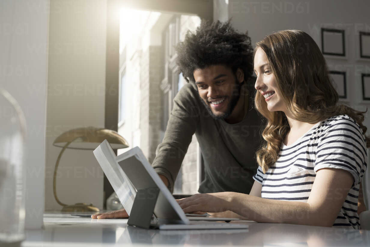 Smiling couple working at home with laptop and tablet - SBOF00409 - Steve Brookland/Westend61