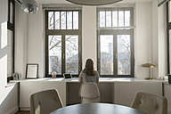 Woman in front of panorama window at home with tablet - SBOF00412