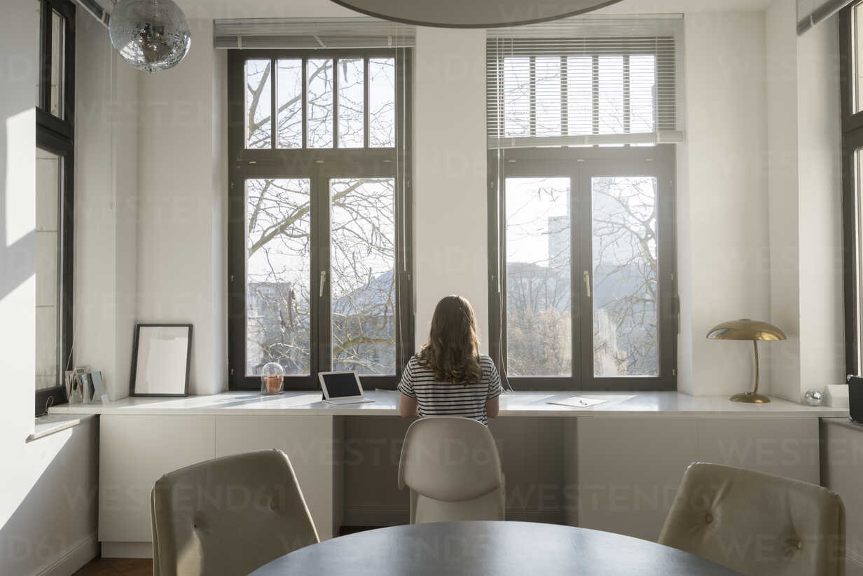 Woman in front of panorama window at home with tablet - SBOF00412 - Steve Brookland/Westend61