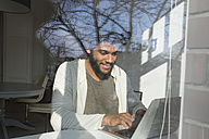 Man working at the window at home with laptop - SBOF00415