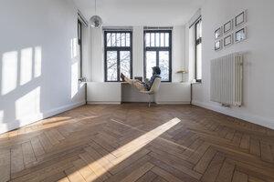 Man sitting in minimalist empty room on chair - SBOF00430