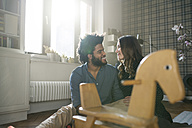 Smiling couple looking at each other in front of rocking horse - SBOF00439