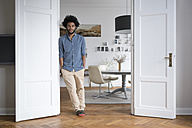 Man at home standing in door frame in living room - SBOF00442