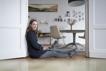 Smiling woman at home sitting on floor working with laptop in door frame - SBOF00445