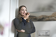 Smiling woman at home leaning in door frame speaking into smartphone - SBOF00448