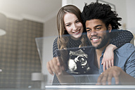 Smiling couple looking at ultra sound picture of baby on futuristic screen - SBOF00451