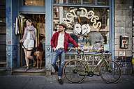 Germany, Hamburg, St. Pauli, Man with bicycle waiting in front of vintage shop, woman with dog coming out - RORF00825