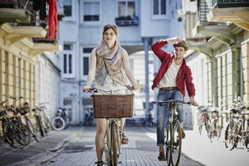 Germany, Hamburg, St. Pauli, Couple exploring the city on their bicycles - RORF00828