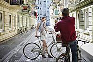 Germany, Hamburg, St. Pauli, Man taking picture of woman with bicycle - RORF00834