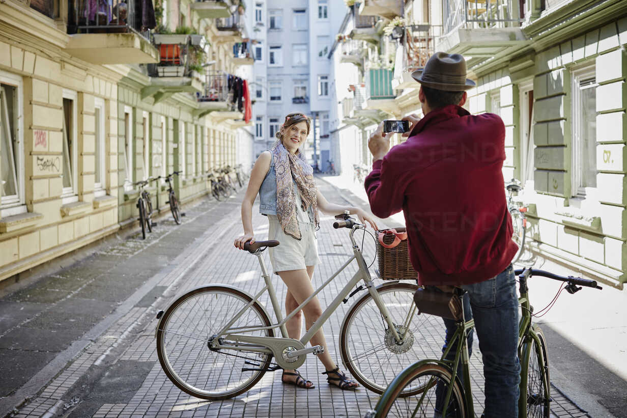Germany, Hamburg, St. Pauli, Man taking picture of woman with bicycle - RORF00834 - Roger Richter/Westend61