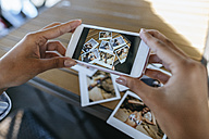 Woman's hands taking picture of instant photos of herself with cell phone - KIJF01452