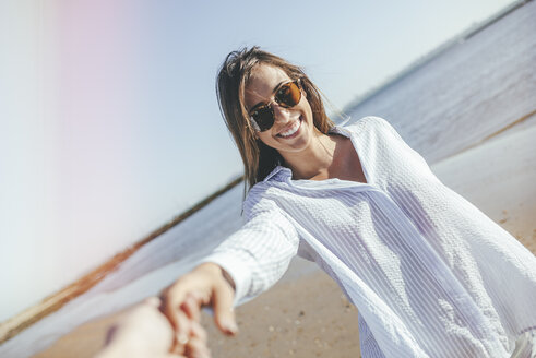 Portrait of smiling young woman with sunglasses holding hand on the beach - KIJF01455