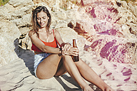 Young woman with bottle of beer relaxing on the beach - KIJF01458