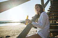 Young woman with bottle of beer relaxing on the beach at sunset - KIJF01464