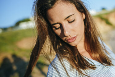 Portrait of young woman with eyes closed at sunlight - KIJF01467