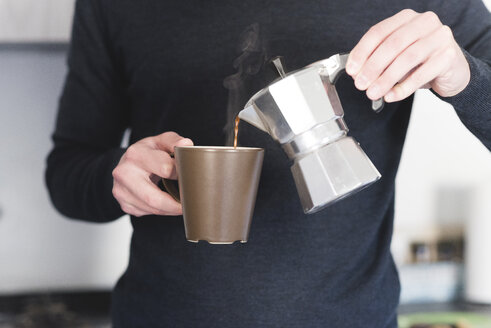 Man pouring hot espresso in a mug, partial view - FMOF00252