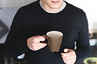 Man with cup of coffee in the kitchen, partial view - FMOF00255