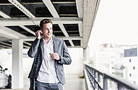 Young businessman using smartphone, walking on parking level - UUF10592