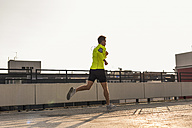 Young man running on parking level - UUF10613