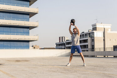 Young man exercising with kettle bell on a rooftop - UUF10622