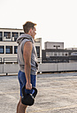 Young man exercising with kettle bell on a rooftop - UUF10625