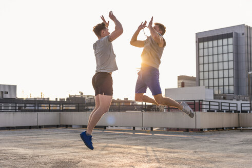 Friends playing basketball at sunset on a rooftop - UUF10631