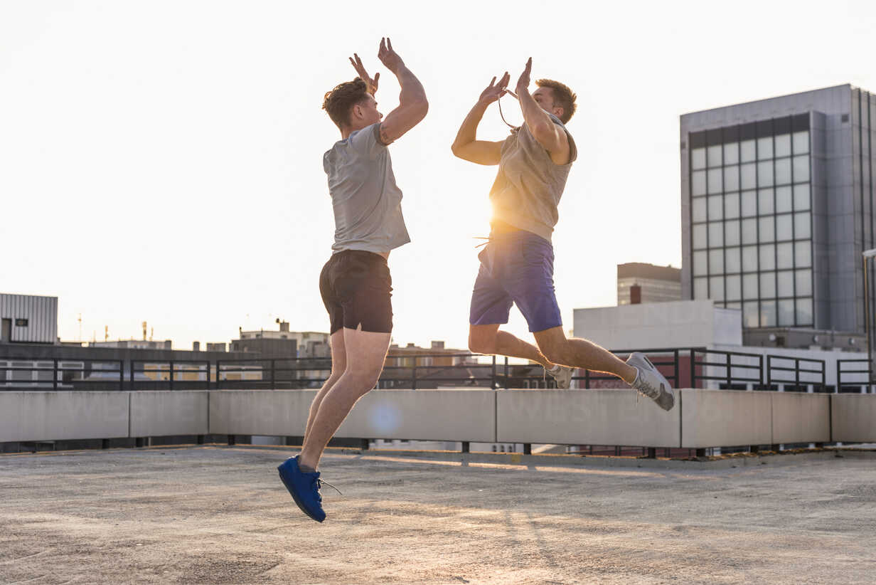 Friends playing basketball at sunset on a rooftop - UUF10631 - Uwe Umstätter/Westend61