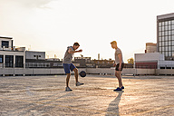 Friends playing basketball at sunset on a rooftop - UUF10637