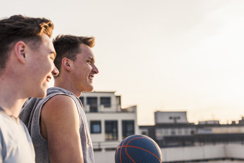 Friends playing basketball at sunset on a rooftop - UUF10640