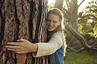 Portrait of smiling young woman hugging tree trunk at backlight - SRYF00430