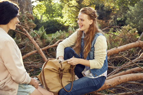 Two young women sitting and talking on tree trunk - SRYF00436
