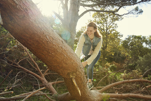Smiling young woman climbing on tree trunk - SRYF00439