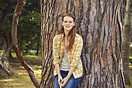 Portrait of smiling young woman leaning against tree trunk - SRYF00448