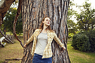Redheaded young woman leaning against tree trunk with eyes closed - SRYF00451