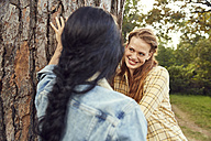 Portrait of redheaded young woman leaning against tree trunk with her friend in the foreground - SRYF00454