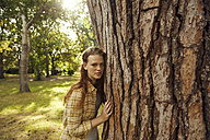Portrait of young woman leaning against tree trunk - SRYF00457