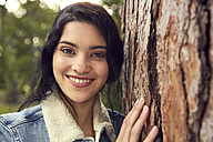 Portrait of smiling young woman beside tree trunk - SRYF00460