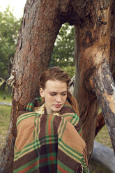 Portrait of young woman in nature wrapped in blanket - SRYF00463
