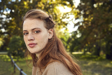 Portrait of redheaded young woman with freckles in a park - SRYF00469