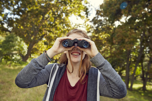 Smiling young woman using binoculars - SRYF00475