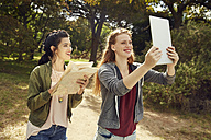 Two young women with tablet and map in nature - SRYF00481