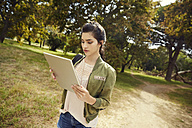 Young woman exploring nature with tablet - SRYF00484