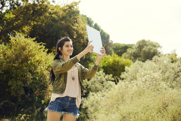 Smiling young woman taking selfie with tablet in nature - SRYF00487