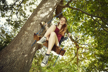 Young woman sitting on a swing - SRYF00493